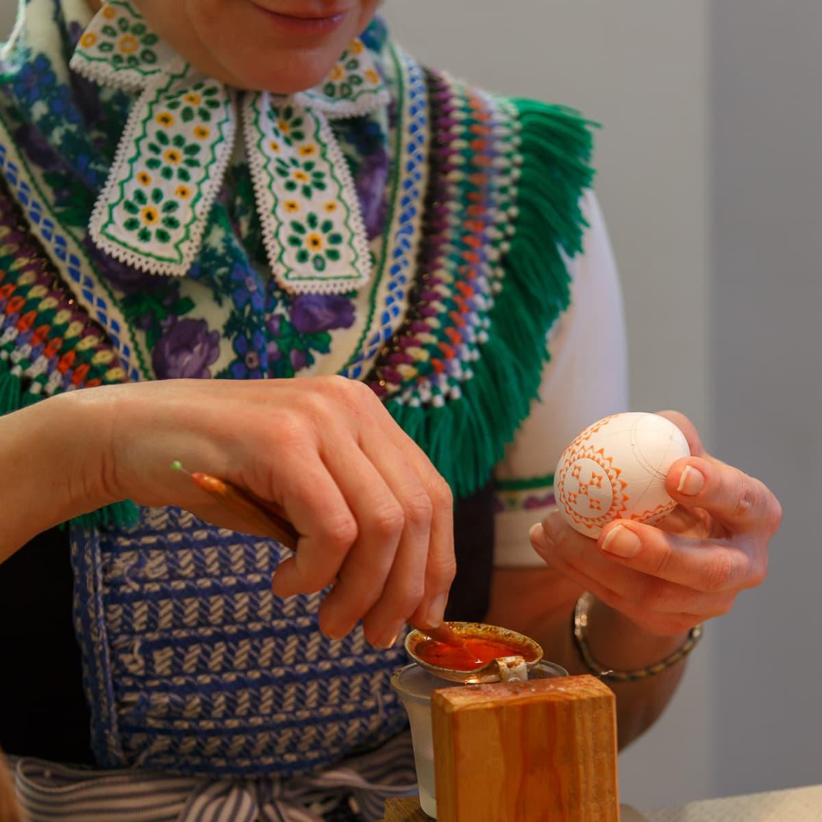 Hände einer Sorbin beim gestalten von sorbischen Ostereiern mit Wachstechnik
