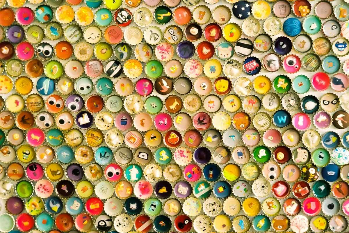 Bunte Kronkorken als Hintergrund an Wand geklebt mit Augen und Figuren